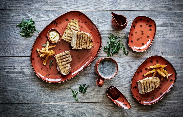 Platos, taza, cuchara y salsera Mature con tostadas y patatas fritas. La colección Mature, del concepto Moods, es un homenaje al calor y la arcilla, una de las materias primas del producto porcelánico. ¡Compra porcelana online!