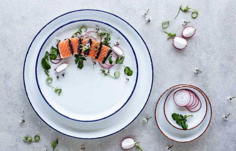 Coleção Coral. Pratos de filagem esponjada azul da coleção Coral Costa Verde com salmão e rabanete.