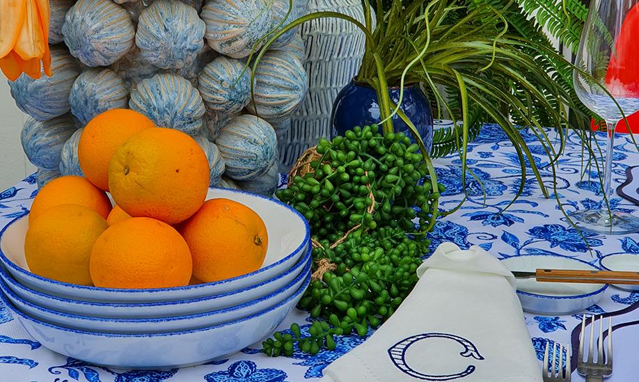 Mesa com laranjas, pratos de porcelana e guardanapos de pano - Detalhes para decorar uma mesa de verão