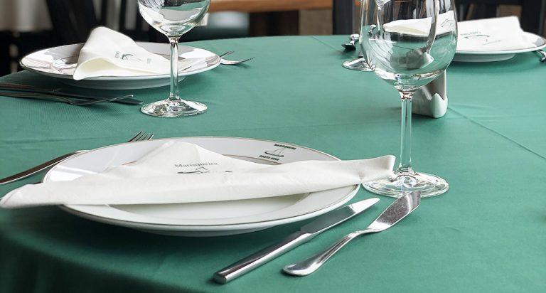Mesa posta no restaurante Marisqueira da Costa com pratos da Costa Verde