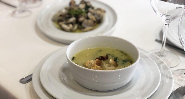 Sopa de peixe servida em pratos e taça da coleção Agma
