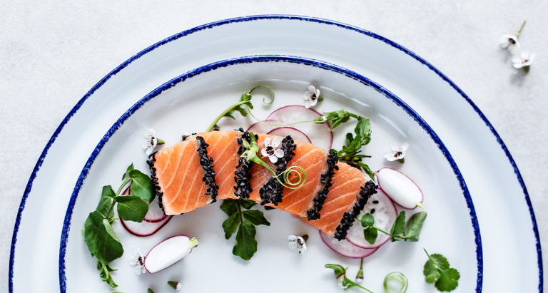 Empratamento com salmão, rabanetes e flores comestíveis num prato da coleção Coral