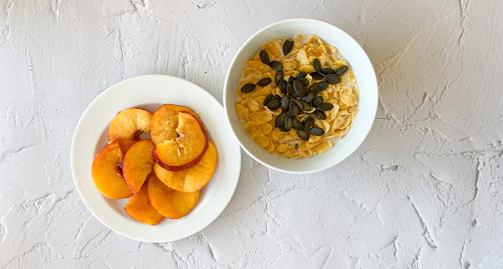 Nectarina servida en un plato de la colección Eclipse y en una cuenco de la colección Nordika con copos de maíz y semillas de calabaza y bebida de soja